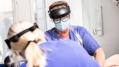 vårdpersonal med visir och munskydd